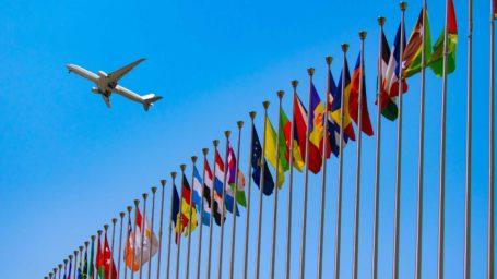 jet flying over international flags